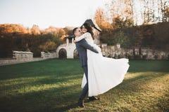 Perfekte Paarbraut, Br?utigam, der in ihrem Hochzeitstag aufwirft und k?sst lizenzfreie stockbilder