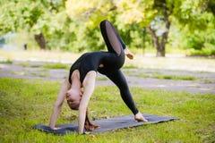 Perfektes acroyoga Schönes junges Mädchen balanciert, Acroyoga tuend Klassentraining der Yogaflexibilität im Freien Stockbild
