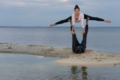 Perfektes acroyoga Schönes junges Paar tut Yoga Stockfotos