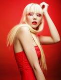 Perfektes blondes Modell im roten Kleid über rotem Hintergrund Stockfotografie