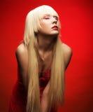Perfektes blondes Modell im roten Kleid über rotem Hintergrund Stockbild