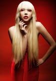 Perfektes blondes Modell im roten Kleid über rotem Hintergrund Lizenzfreie Stockbilder