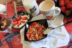 Perfektes Frühstück: knuspriges Granola mit Jogurt und Erdbeeren mit einer Schale Milchkaffee auf Marmortabelle Guten Morgen verw stockbilder