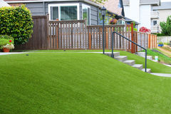 Perfektes Gras, das mit künstlichem Gras im Wohngebiet landschaftlich gestaltet lizenzfreie stockfotos