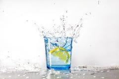 Perfektes Zitronenspritzen in einem blauen Glas Wasser stockfotos