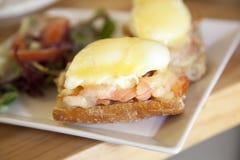 Perfezioni la prima colazione calda - uova affogate al forno con formaggio e fumo Immagine Stock