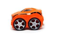Perfil anaranjado del coche de carreras del juguete Fotos de archivo
