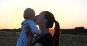 Perfil animador de uma mãe nova que mantém seu bebê nas mãos no por do sol no slo-mo video estoque