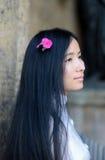 Perfil asiático da menina com a flor em seus cabelos Fotos de Stock Royalty Free