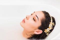 Perfil da cara da mulher do close up que encontra-se em um banho do leite fotos de stock royalty free