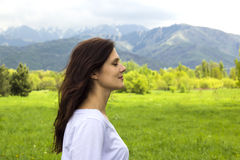 Perfil da jovem mulher com ar fresco de respiração fechado dos olhos nas montanhas Fotos de Stock Royalty Free
