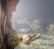 Perfil da menina que olha seu pássaro de voo de imaginação móvel Imagens de Stock