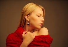 Perfil de la chica joven que lleva la bufanda roja en fondo negro Fotos de archivo