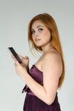Perfil de la chica joven que usa un teléfono móvil El llevar Redheaded de la muchacha Foto de archivo libre de regalías