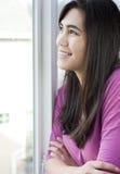 Perfil de la muchacha adolescente que mira hacia fuera la ventana Imagenes de archivo