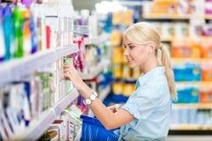 Perfil de la muchacha en la tienda que elige los cosméticos Fotografía de archivo