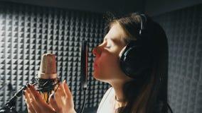 Perfil de la muchacha hermosa que canta en estudio de los sonidos Cantante joven que registra emocionalmente la nueva canción La  almacen de video