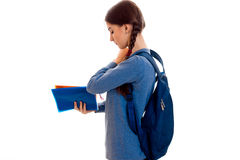 Perfil de la muchacha morena feliz elegante del estudiante con la mochila azul y de la carpeta para los cuadernos en su presentac Foto de archivo