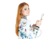Perfil de la muchacha que usa el teléfono móvil y escuchando la música Redheade Imagen de archivo libre de regalías