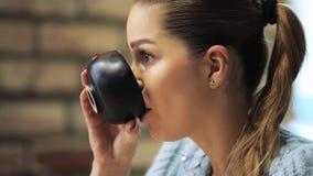 Perfil de la mujer hermosa que escucha un interlocutor en un café metrajes