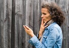 Perfil de la mujer madura con el teléfono Foto de archivo libre de regalías