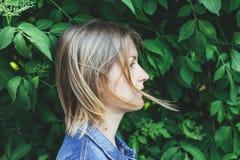 Perfil de la mujer rubia al lado de los árboles fotos de archivo libres de regalías