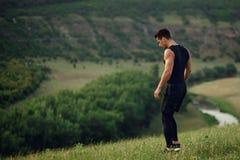 Perfil de um atleta, homem muscular, apto, novo que faz esticando exercícios antes do exercício fora no fundo da floresta imagens de stock