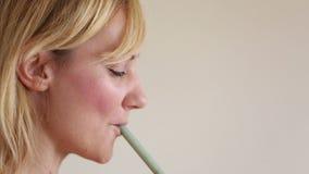 Perfil de um batido bebendo da mulher com uma palha video estoque