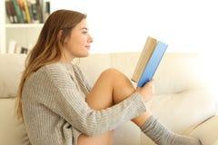 Perfil de uma leitura adolescente um livro em casa imagens de stock royalty free