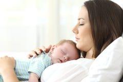 Perfil de uma mãe séria que dorme com seu bebê foto de stock royalty free
