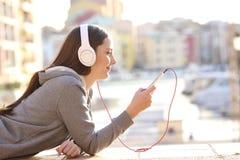 Perfil de uma menina adolescente que escuta a música imagens de stock royalty free