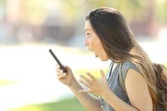 Perfil de uma mulher surpreendida que usa um telefone Fotografia de Stock