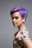Perfil de uma mulher violeta-curto-de cabelo dentro, olhando o camer Foto de Stock