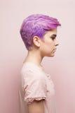 Perfil de uma mulher violeta-curto-de cabelo na cor pastel cor-de-rosa Fotografia de Stock Royalty Free