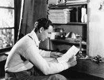 Perfil de un hombre joven que lee un papel en su escritorio (todas las personas representadas no son vivas más largo y ningún est Fotografía de archivo libre de regalías