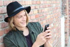 Perfil de un individuo feliz que usa un teléfono elegante que se sienta afuera con el espacio para la copia Fotos de archivo