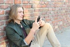 Perfil de un individuo feliz que usa un teléfono elegante que se sienta afuera con el espacio para la copia Imagen de archivo libre de regalías