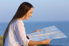 Perfil de un turista que consulta un mapa de la guía en la playa Foto de archivo