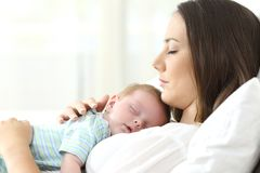 Perfil de una madre seria que duerme con su bebé foto de archivo libre de regalías