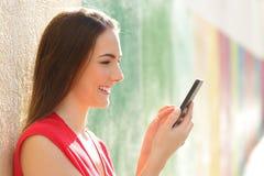 Perfil de una muchacha que comprueba el teléfono en una calle colorida fotos de archivo libres de regalías