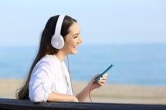 Perfil de una muchacha que escucha la música en la playa Fotos de archivo libres de regalías