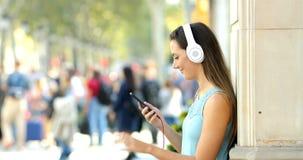 Perfil de una muchacha que escucha la música de un teléfono en la calle almacen de video