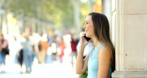 Perfil de una muchacha que habla en el teléfono en la calle