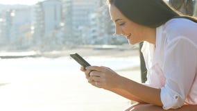 Perfil de una muchacha que usa el teléfono elegante en la costa metrajes