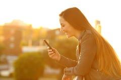 Perfil de una muchacha que usa un teléfono elegante en la puesta del sol Fotografía de archivo