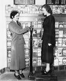 Perfil de una mujer joven en un peso de medición uniforme de otra mujer joven en una balanza (todas las personas representadas no Imagen de archivo libre de regalías