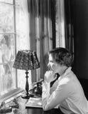 Perfil de una mujer joven que se sienta en un escritorio y que mira a través de una ventana (todas las personas representadas no  fotos de archivo