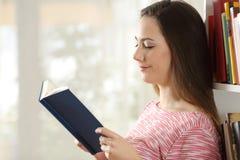 Perfil de una mujer que lee un libro en casa Imagen de archivo