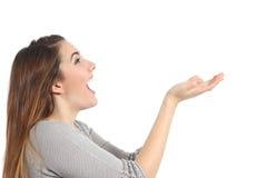 Perfil de una mujer que lleva a cabo algo en blanco sorprendido Imagen de archivo libre de regalías