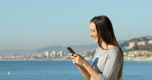 Perfil de una mujer que manda un SMS en el teléfono en la playa